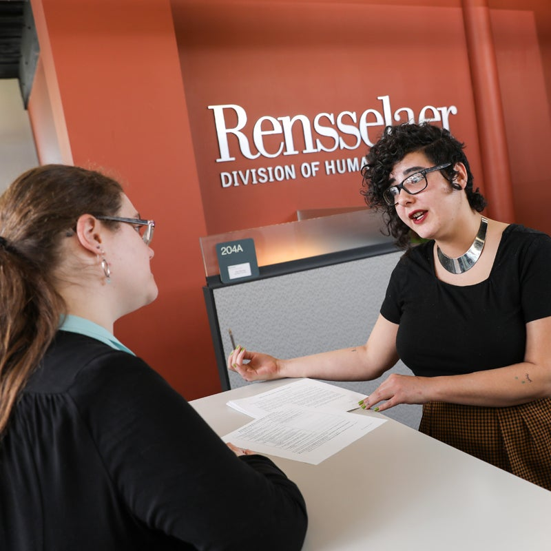 Women at Receptionist Desk in Discussion with Employee